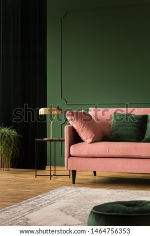 Stylish golden lamp on industrial table next to pink couch with emerald pillows in dark green living room interior,copy space on empty wall