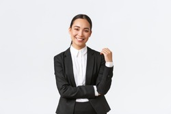 Stylish good-looking female broker selling houses to clients. Asian businesswoman in suit smiling happy and looking confident. Successful manager during work, white background