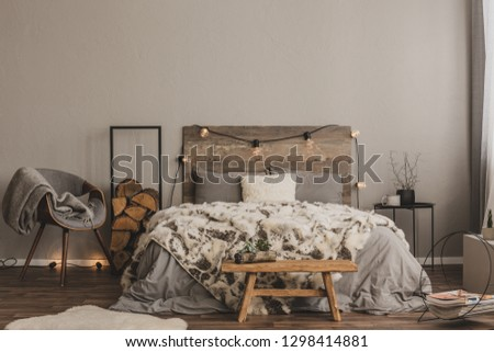Stylish grey chair with blanket and log of wood next to warm double bed with wooden headboard and light bulbs #1298414881