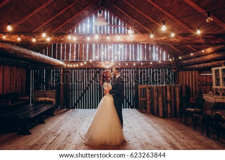 Shutterstock stylish groom and happy bride hugging under retro bulbs lights in wooden barn. rustic wedding concept, space for text. newlyweds couple embracing, sensual romantic moment