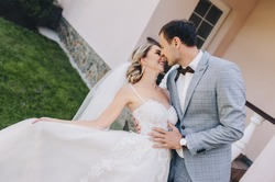 Stylish groom in a gray checkered suit tilts in a mobile dance a cute blonde bride in a white lace dress with a long veil in a park near an old house. Wedding portrait of smiling newlyweds.