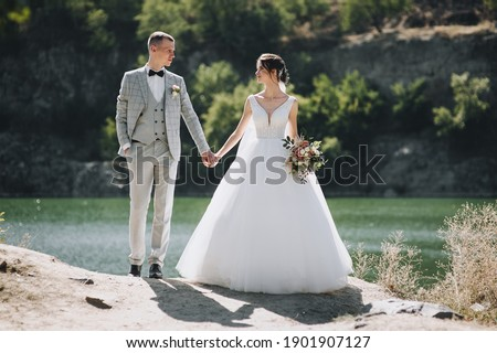 Stylish groom in a gray tailcoat with a black bow tie and a beautiful, curly-haired bride in a white long dress are standing holding hands near the river and rocks. Wedding portrait of newlyweds. Photo stock ©