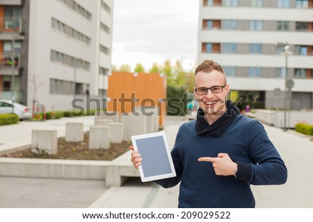 Stylish guy connected on internet with tablet in town. He is happy. He is pointing on tablet pc