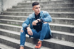 Stylish guy standing street in a denim jacket against sitting on the stairs, men's looks