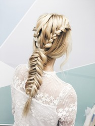 Stylish hairstyle. Closeup blonde girl in white dress. Boho braid. Wedding hairstyle.
