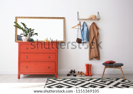 Stylish hallway interior with mirror and chest of drawers #1151369105