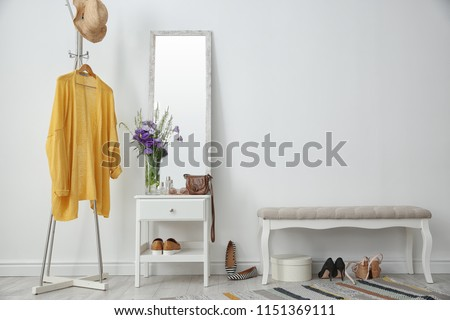 Stylish hallway interior with mirror and rack #1151369111