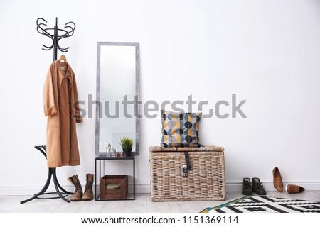 Stylish hallway interior with mirror and rack