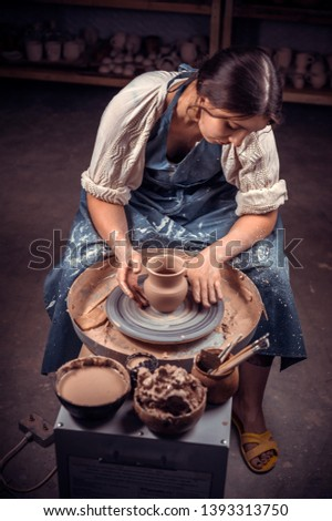 Stylish handicraftsman master making pottery, sculptor from wet clay on wheel. Artisan production.