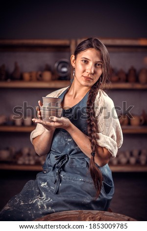 Stylish handicraftsman master shows how to work with clay and pottery wheel. Handicraft industry. Stock fotó ©