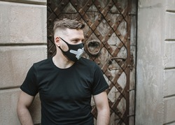 Stylish handsome guy in a black protective mask. Original face masks to protect against infection.