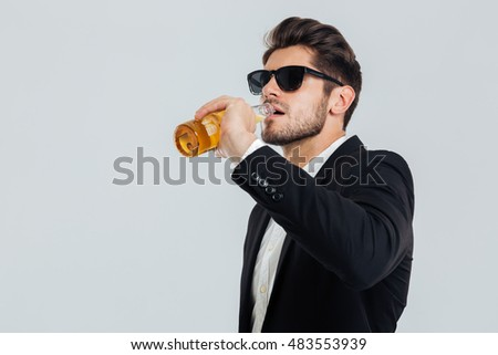 Stylish handsome man in sunglasses and black suit drinking from beer bottle over grey background #483553939