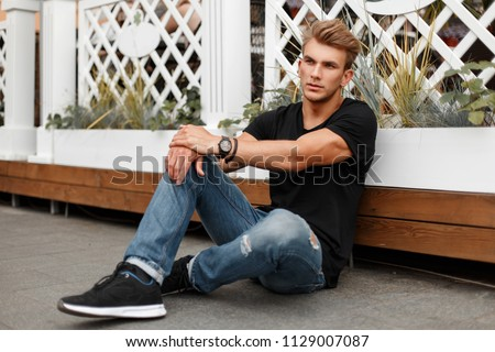 Stylish handsome young man in black T-shirt with jeans and shoes sitting on the beach #1129007087