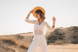 stylish happy attractive smiling woman posing in desert sand dressed in white clothes wearing straw hat and sunglasses on sunset, travel safari on vacation, sunny summer day