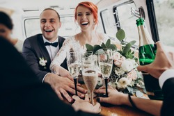 stylish happy bride and groom toasting with glasses of champagne and having fun with bridesmaids and groomsmen inside of retro car. emotional moment, space for text. wedding party