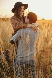 Stylish happy couple dancing in warm sunset light in autumn field. Young fashionable woman and man twirling among grass and herbs in sunshine. Romantic authentic moment