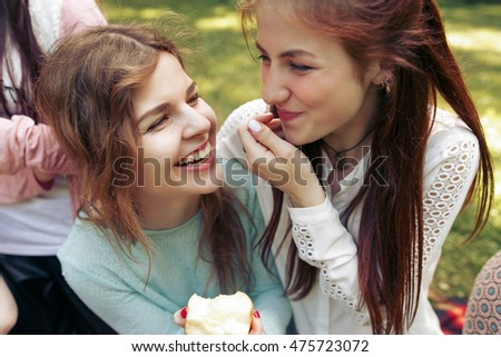 stylish happy group of women eating fruits and having fun smiling on picnic, joyful moments in summer park #475723072
