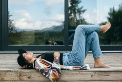 Stylish happy woman relaxing on wooden terrace on background of modern cabin with windows. Young female in casual cloth and hat lying on porch in mountains. Calm tranquil moment. Travel