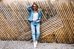 Stylish happy young woman wearing boyfrend jeans and white sneakers with hand in pocket. Full-length portrait of smiling girl in sunglasses and denim suit isolated on wooden fence background.