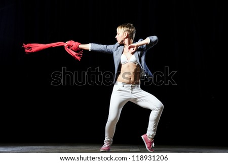 Stylish hip-hop female dancer performs on the stage on black background.