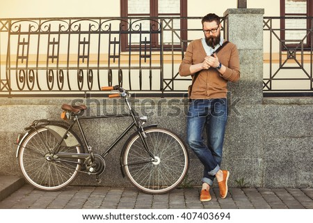 stylish hipster bearded man in the street bike leather handbag, glasses. Vintage style photography, lighting effects. Old european city