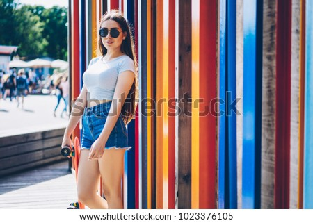 Stock Photo Stylish hipster girl in sunglasses standing near colorful promotional background.Young woman in casual summer clothes holding skateboard in hands near publicity area for your advertising