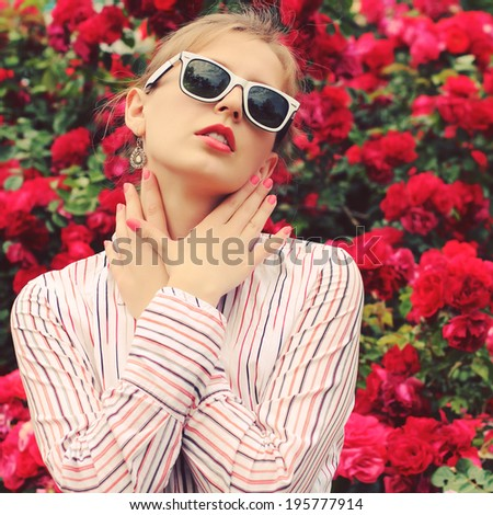 Stylish hipster girl in trendy glasses. Glamorous photo shoot in a chic outdoor garden. Photo toned style Instagram filters