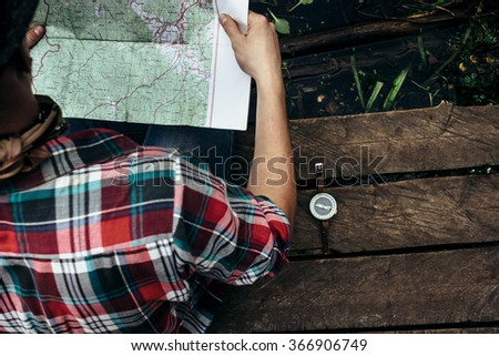 stylish hipster traveler exploring map at sunny forest and lake in the mountains