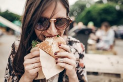 stylish hipster woman holding juicy burger and eating. boho girl biting hamburger  smiling at street food festival. summertime. summer vacation travel. space for text