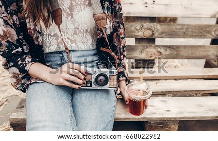 stylish hipster woman holding lemonade and old photo camera. boho girl in denim and bohemian clothes, holding cocktail sitting on wooden bench at street food festival. summertime #668022982