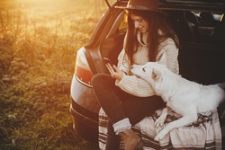 Stylish hipster woman in hat and sweater holding phone and sitting with cute dog in car trunk in sunset light. Travel and road trip with pet. Young female with smartphone in evening autumn field