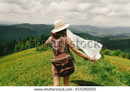 stylish hipster woman traveler with backpack holding map and exploring on top of mountains, travel  concept, space for text. wanderlust