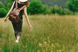 stylish hipster woman walking in grass and holding  in hand herb  wildflowers  in summer mountains, travel concept, peaceful relaxing moment. happy earth day