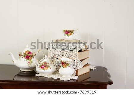 Stylish home decor arrangement with flowers, crystal, china, books, and an antique doily.