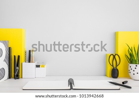 Stylish home office desk with copy space, books, office supplies. Yellow, grey mock up.