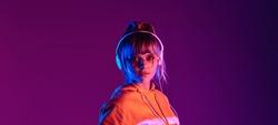 Stylish igen teen hipster pretty fashion girl model wear glasses headphones enjoy listen new dance music mix look at camera at purple studio background trendy 80s party light, portrait website banner