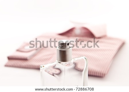 Stylish image of a bottle of scent an a nice man's shirt