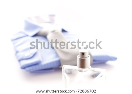 Stylish image of a bottle of scent with a mans shirt in the background