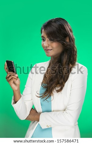 Stylish Indian Woman using a smart phone. Young and fresh Asian female model a bright green background.