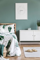 Stylish interior design of bedroom with wooden bed, mock up poster frame, rattan white shelf , plants and elegant accessories. Beautiful bed sheets, blanket and pillow. Template. Design home decor