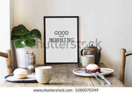 Stylish interior design of kitchen space with small table with mock up frame, plant, cups of tea and tasty dessert.