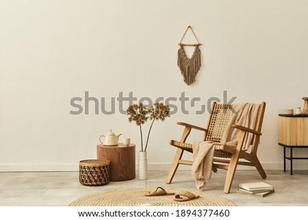 Stylish interior design of living room with wooden armchair, coffee table, furniture, rattan decoration, dried flowers and elegant personal accessories. Copy space white wall. Template.