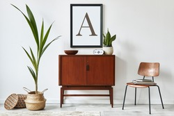 Stylish interior design of living room with wooden retro commode, chair, tropical plant in rattan basket, decoration and elegant personal accessories. Mock up poster frame on the white wall. Template