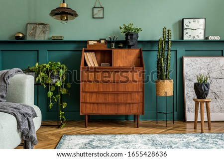 Stylish interior design with retro wooden cabinet, chair, gray sofa, plants, pendant lamp, decoratnion, organizer, stool and elegant personal accessories. Modern retro concept of home office space.
