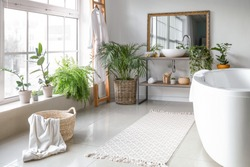 Stylish interior of bathroom with green houseplants