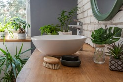 Stylish interior of bathroom with green plants as a natural jungle and window at bright home. Design bathroom with washbasin on wooden counter and mirror. Close up.
