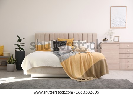 Stylish interior of contemporary room with comfortable bed