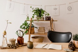 Stylish interior of home office space with wooden desk, forest accessories, avocado plant, bamboo shelf with a lot of plants and rattan baskets. Nice drawings on the white wall. Botanical home decor