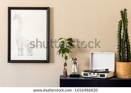 Stylish interior of living room with black mock up poster frame, blue navy commode, gramophone, avocado plant, cacti and elegant personal accessories. Beige walls. Modern home decor. Template.