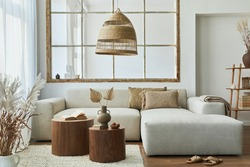 Stylish interior of living room with design modular sofa, furniture, wooden coffee table, rattan decoration, pendant lamp, pillow, dried flowers and elegant accessories in modern home decor.